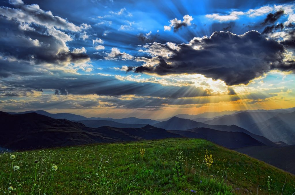 mountain scene with the sky showing partly cloudy with sun shining from behind clouds